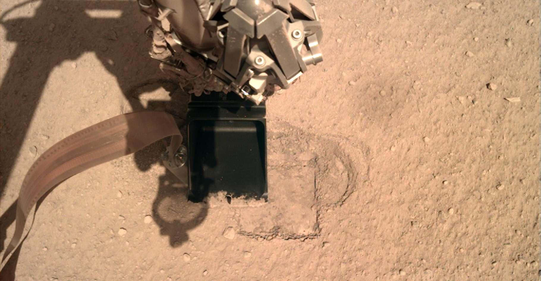 Ici, le bras robotisé de l'atterrisseur InSight qui presse le capteur de flux thermique HP3 afin de lui offrir la résistance suffisante à lui permettre de creuser le sol de Mars. © Nasa, JPL-Caltech