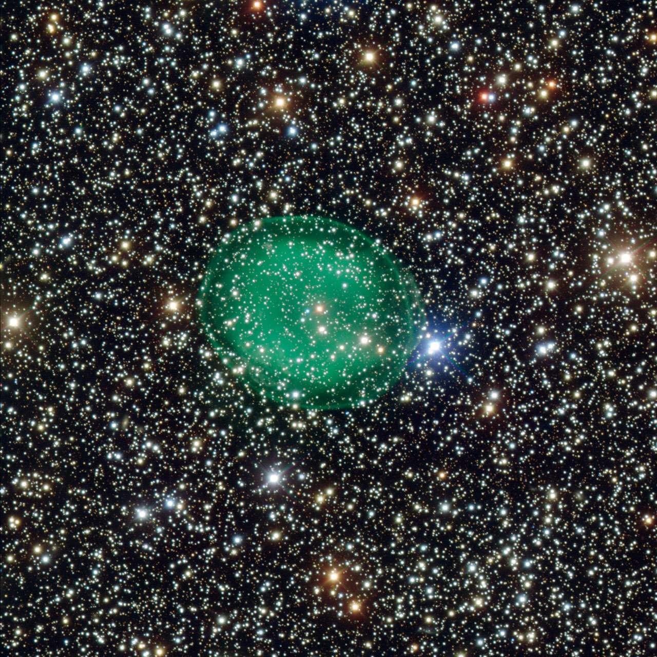 Cette étonnante image obtenue grâce au très grand télescope de l'ESO, le VLT, montre la nébuleuse planétaire verte et éclatante IC 1295 entourant une étoile de faible luminosité en fin de vie. Les restes consumés de l'étoile se situent au centre de la nébuleuse, en un point couleur bleu-blanc. © ESO