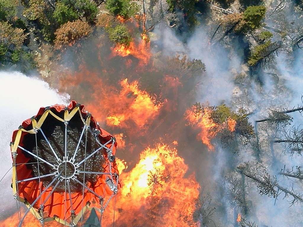 Les hélicoptères vont au plus près du feu pour larguer l'eau. Pour être reconnaissables par les Hommes au sol et faciliter la communication, des dessins (par exemple une bouche souriante et deux yeux) sont peints en jaune sous les carlingues. © Colorado National Guard