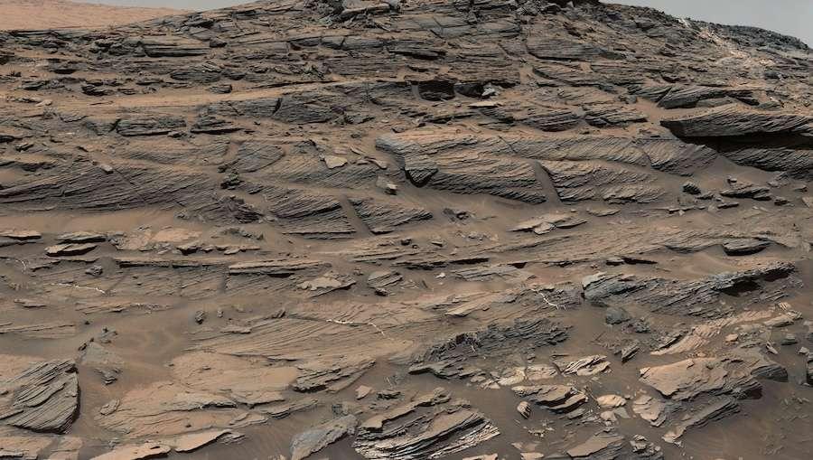 Cette photo est constituée de plusieurs images prises le 27 août 2015 (Sol 1.087) par les deux caméras du mât de Curiosity. Cette couche de grès, sur le Mont Sharp, actuellement explorée par le rover est nommée unité Stimson. On y voit des dunes de sable pétrifiées. Les lignes indiquent la direction des vents dominants. La balance des blancs a été travaillée de façon à faire apparaître le paysage sous un éclairage solaire comparable à celui de la Terre. Téléchargez l'image complète et en haute résolution ici (2,32 Mo). © Nasa, JPL-Caltech, MSSS