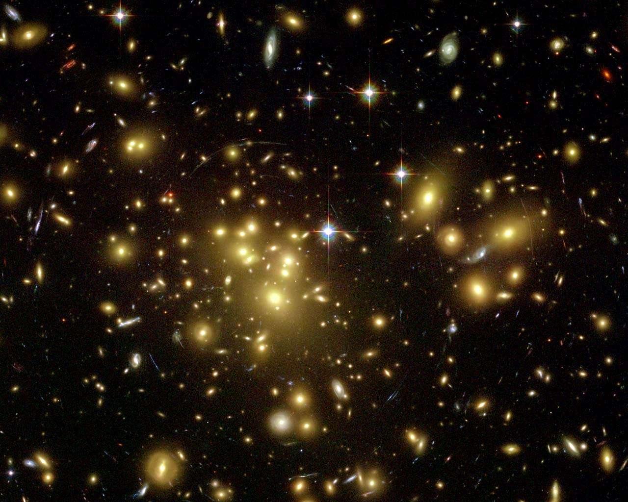 Abell 1689 est un amas de galaxies dans la constellation de la Vierge. C'est l'un des plus grands amas et un des plus massifs avec effet de lentille gravitationnelle, trahissant la présence de matière noire. Il est distant de 2,2 milliards d'années-lumière et contient environ 1.000 galaxies. © Nasa