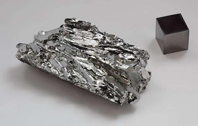 Le molybdène est notamment utilisé pour durcir les aciers. Ici, un fragment de molybdène cristallin ainsi qu'un cube d'1 cm3. © Alchemist-hp, Wikimedia Commons, CC by-nc-nd 3.0