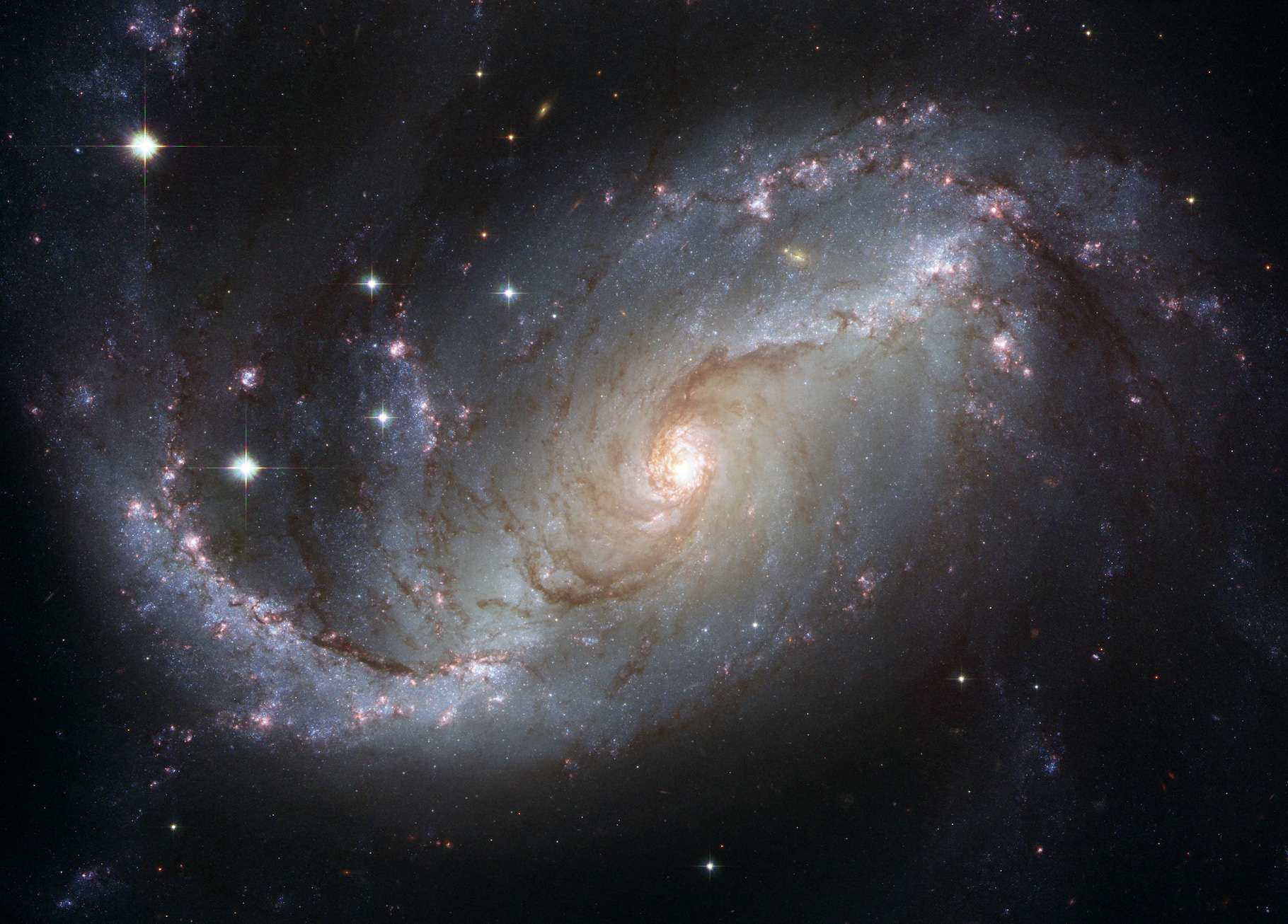 Cette image composite de la galaxie spirale barrée NGC 1672 a été réalisée en utilisant des filtres qui isolent la lumière des parties bleues, vertes et infrarouges du spectre ainsi que l'émission de l'hydrogène ionisé. © Nasa, ESA, The Hubble Heritage Team (STScI/AURA)-ESA, Hubble Collaboration