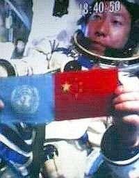 Dans son vaisseau en orbite autour de la Terre, Yang Liwei brandit le drapeau des Nations Unies et le drapeau chinois.