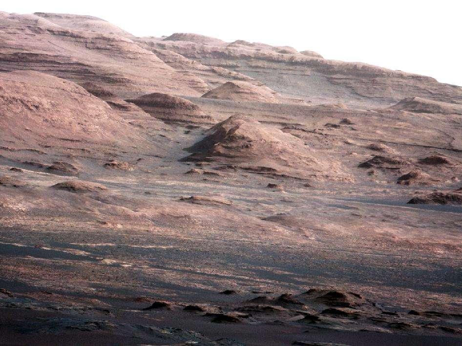 Les flancs du mont Sharp photographiés le 28 août 2012, peu après l'arrivée de Curiosity. On remarque la structure en strates. Ces dépôts sédimentaires ont probablement beaucoup de choses à nous raconter sur le passé de Mars et en particulier sur cette époque où la planète était plus chaude et plus humide. Curiosity a commencé à lire les premiers chapitres de cette histoire. © Nasa, JPL-Caltech