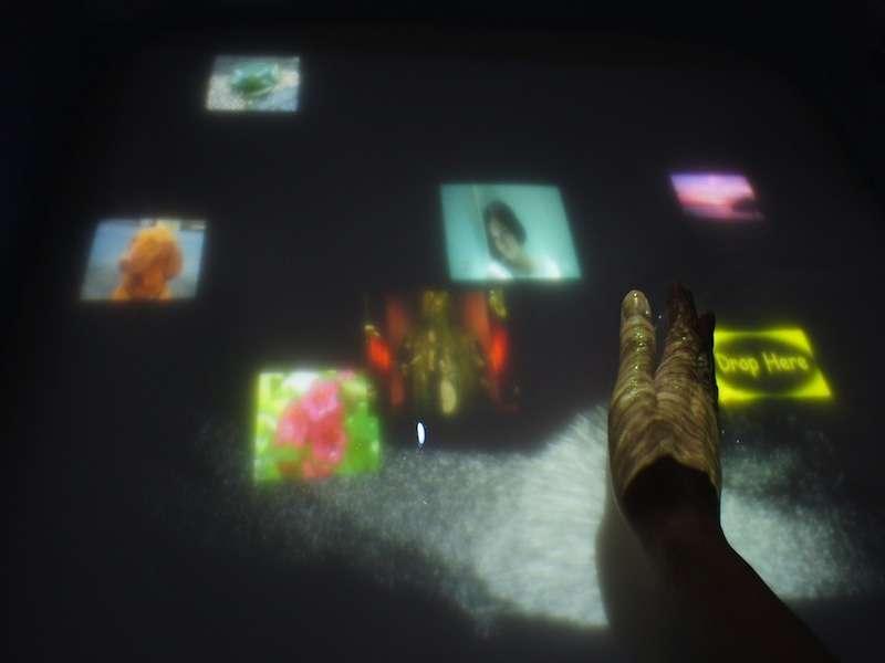 L'un des avantages de la technologie AquaTop est que l'on peut interagir avec la surface tactile non seulement sur, mais par en dessous. Par exemple, pour supprimer une image ou un fichier, il suffit de le saisir au creux de la main puis de le faire couler. © Laboratoire d'électrocommunication de l'université de Tokyo, YouTube