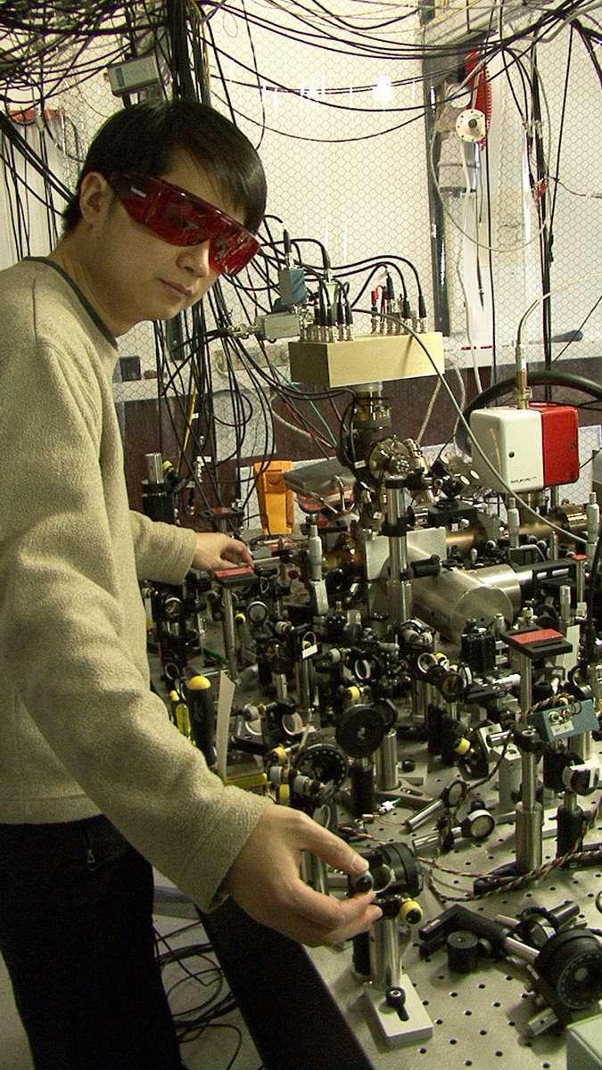 James Chin-Wen Chou, du NIST, devant l'horloge atomique la plus précise au monde, basée sur les vibrations d'un seul ion aluminium. L'ion est piégé à l'intérieur du cylindre métallique (centre droit). © J. Burrus/NIST