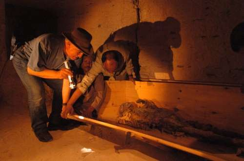 Zahi Hawass observant la momie de la reine Hatchepsout. On remarque son bras gauche replié sur la poitrine, une position habituellement réservée aux pharaons. Crédit : Musée du Caire / Zahi Hawass