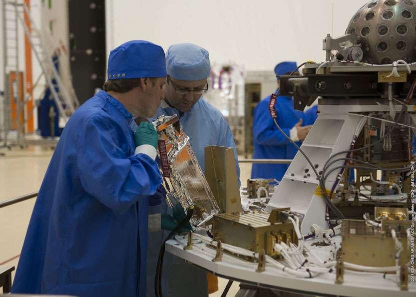 Installation des satellites pour le tir VV01 du lanceur Vega (13 février 2012). L'opérateur est en train de placer un nanosatellite CubeSat dans un canister, conteneur métallique. © Esa, CSG, Arianespace, Optique Vidéo du CSG, J. M. Guillon