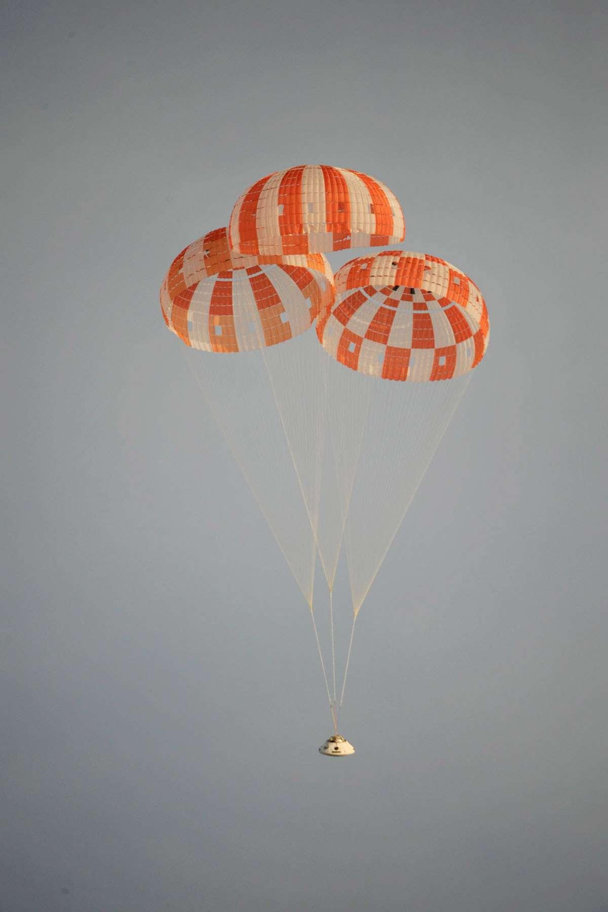 Parachutes principaux déployés, la capsule Orion-MPCV, stabilisée par un système ad hoc descend en sécurité pour se poser sans dommage sur la terre ferme. © Nasa