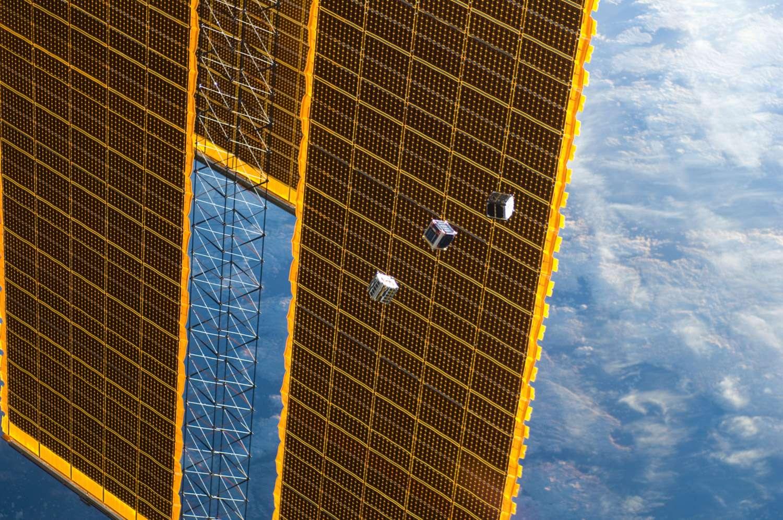 Trois des cinq petits satellites largués depuis la Station spatiale internationale, ici vus devant un des panneaux solaires de l'ISS. © Nasa