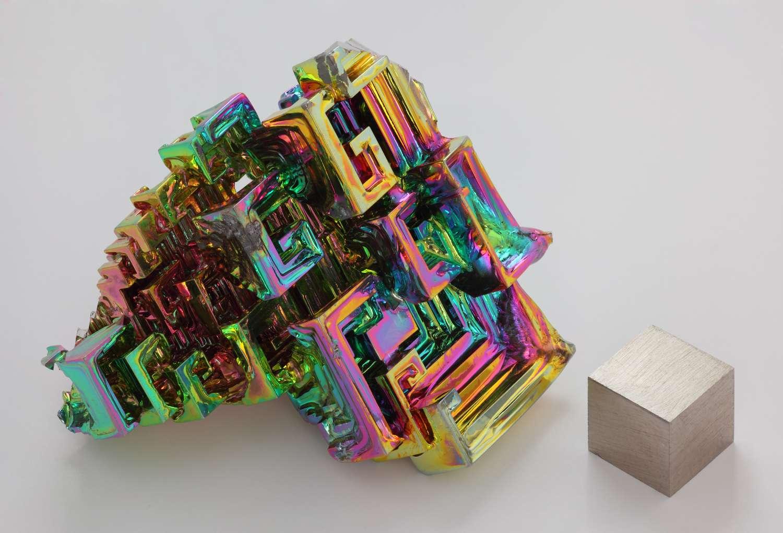 Cristal obtenu par cristallogenèse artificielle de bismuth métallique à coté d'un cube d'1 cm3 de bismuth pur à 99,99 %. L'irisation est due à une couche d'oxyde très mince. © Alchemist-hp, Wikiemdia Commons, CC by-nc-nd 3.0