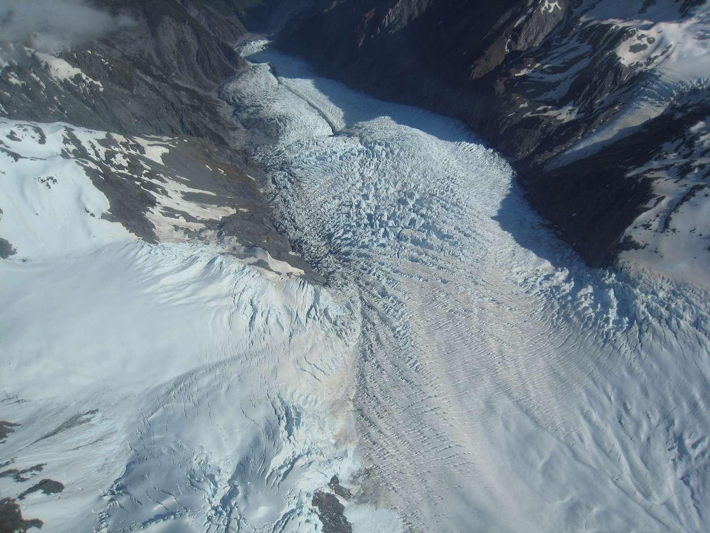 Vue aérienne du glacier Franz Josef qui s'étend sur environ 10 km et glisse à une vitesse pouvant atteindre 2 m/j sur un substrat rocheux composé de schistes métamorphiques. Ces schistes contiennent les matériaux graphitiques utilisés pour tracer la provenance des particules sédimentaires dans le ruisseau sous-glaciaire. © Avenue, Wikimedia Commons, CC BY-SA 3.0