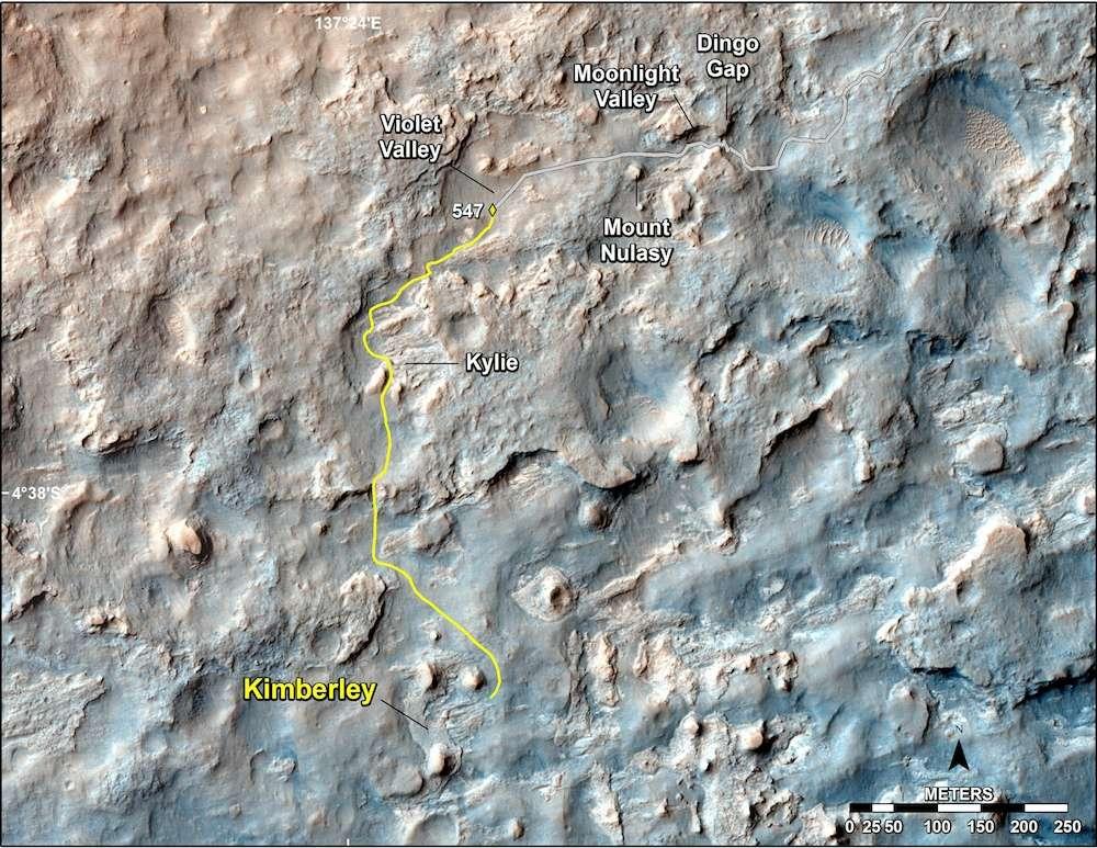 Sur cette image de la caméra HiRise (High Resolution Imaging Science Experiment) de la sonde spatiale Mars Reconnaissance Orbiter (MRO), on découvre le contexte topographique où progresse actuellement Curiosity. La dune Dingo Gap fut franchie lors de son 535e jour sur Mars (sol 535). Depuis, le rover emprunte un nouvel itinéraire, moins périlleux, et roule à reculons en direction du site Kimberley, distant de 1,1 kilomètre. Le 18 février, il a parcouru plus de 100 mètres en une seule journée. © Nasa, JPL-Caltech, université d'État de l'Arizona