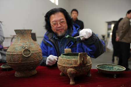 Liu Daiyun, archéologue, montre ce qui ressemble à un os animal, sorti de ce chaudron en bronze daté de 2.400 ans. © CFP