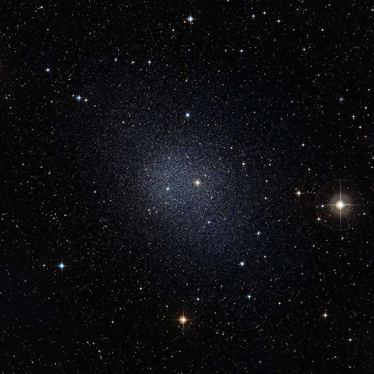 D'après le modèle de la matière noire froide, les galaxies naines contiendraient une masse sous forme de nouvelles particules inconnues mille fois plus importante que la matière visible sous forme d'étoiles et de nuages d'hydrogène (dans le cas de la Voie lactée, ce rapport est de dix environ). Les galaxies naines de la Voie lactée, comme celle du Fourneau (à l'image), sont donc de bons laboratoires pour tester la théorie de la matière noire. Jusqu'à présent, les observations et la théorie étaient en contradiction concernant la répartition de la matière noire dans ces galaxies. Ce problème vient peut-être de trouver un début de solution. © Eso