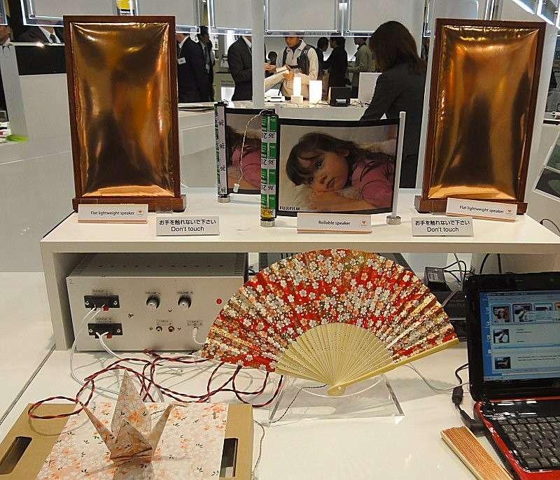 À l'occasion du salon Nano Tech 2013 qui s'est tenu à Tokyo au Japon, Fujifilm a présenté sa technologie de haut-parleur souple. Il s'agit d'un film combinant polymères et céramique piézoélectrique qui allie souplesse et dureté pour résonner comme la membrane d'un haut-parleur. On voit sur cette photo les diverses formes que le film peut prendre : un éventail, plié en origami, en cylindre déroulable ou en panneau ultra fin. © Fujifilm/Tech-On