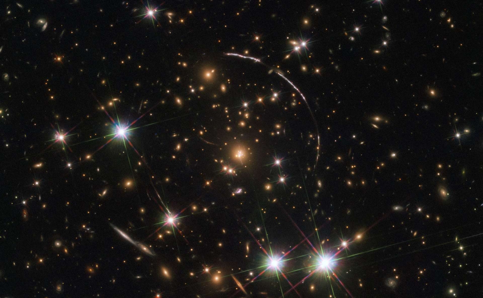 Cette image, prise avec le télescope spatial Hubble Nasa-ESA, montre un gigantesque amas de galaxies situé à environ 4,6 milliards d'années-lumière. Le long de ses frontières, quatre arcs lumineux sont visibles. Ce sont des copies de la même galaxie lointaine surnommée Arc Sunburst. La galaxie Sunburst Arc est à près de 11 milliards d'années-lumière. Trois arcs sont visibles en haut à droite de l'image, le quatrième en bas à gauche. Le dernier est partiellement masqué par une étoile brillante au premier plan, située dans la Voie lactée. © ESA, Hubble, Nasa, Rivera-Thorsen et al.