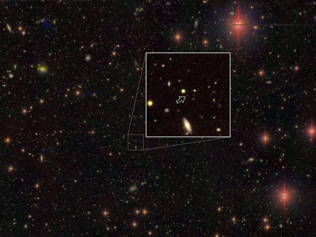 On relève parmi les 83 quasars nouvellement découverts, le troisième quasar le plus distant connu, dit HSC J1243+0100 (minuscule point rouge indiqué par une flèche), à une distance de 13,05 milliards d'années-lumière de nous, et aussi un des moins lumineux (publication de 2019). Il est vu ici par la caméra en lumière visible à grand champ Hyper Suprime-Cam (HSC) du télescope Subaru de l'Observatoire astronomique national du Japon (NAOJ). En son sein, se terre un trou noir de 300 millions de masses solaires. Des étoiles de la Voie lactée et d'autres galaxies figurent également sur l'image. © National Astronomical Observatory of Japan (NAOJ)