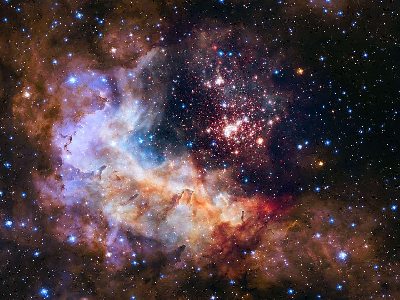 Dans la nébuleuse Gum 29 qui se profile devant l'essaim de jeunes étoiles Westerlund 2, se dressent des piliers de gaz hérissés, tous érodés par les vents violents des astres les plus massifs. Ce merveilleux tableau composite mélange des images prises dans le visible et le proche infrarouge avec les caméras ACS et WFC3 du télescope spatial qui fête, le 24 avril, ses 25 ans dans l'espace. © Nasa, Esa, the Hubble Heritage Team (STScI/AURA), A. Nota (ESA/STScI), the Westerlund 2 Science Team