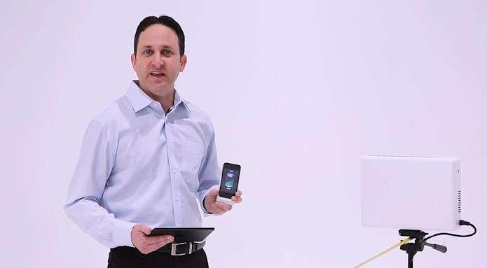 La technologie de charge sans fil WattUp mise au point par la start-up Energous repose sur un transmetteur (boitier blanc que l'on voit sur le trépied) et un récepteur qui est intégré dans une coque externe dans laquelle on glisse le smartphone ou la tablette. Le transmetteur utilise une liaison Bluetooth pour identifier les appareils et peut en charger deux simultanément jusqu'à une distance de 4,5 mètres. © Energous