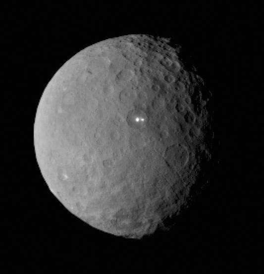 Dawn était à environ 46.000 km de sa destination, la planète naine Cérès, le 19 février lorsque sa caméra a pris cette image. Le point blanc remarqué depuis son approche, il y a quelques semaines, apparait double à l'intérieur d'un cratère. © Nasa, JPL-Caltech, Ucla, MPS, DLR, IDA