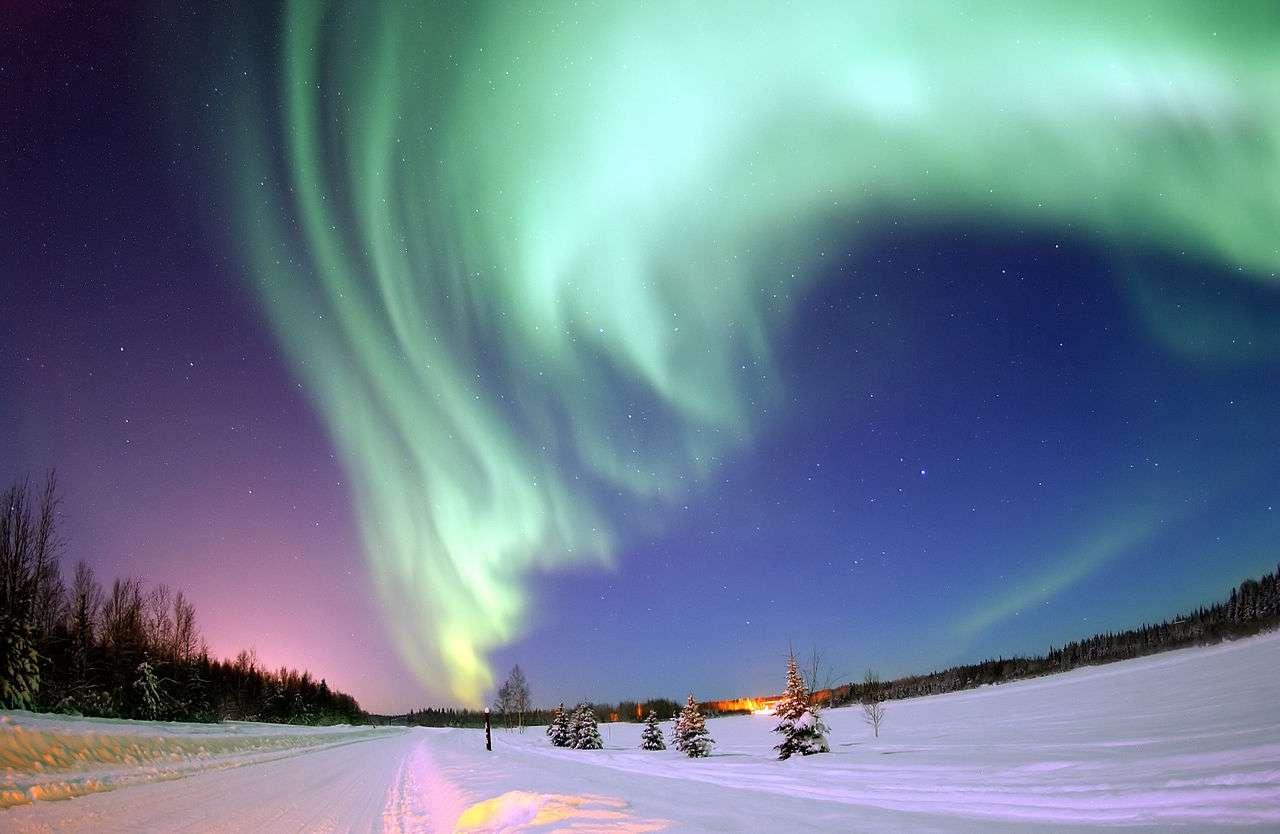 Une aurore boréale brille au-dessus de Bear Lake, près de la base de l'US Air Force d'Eielson, en Alaska. Le parc canadien Wood Buffalo est devenu la plus grande réserve mondiale de ciel étoilé, et permettra au visiteur de profiter pleinement de ce type de phénomène. © Joshua Strang, Wikimedia Commons, DP