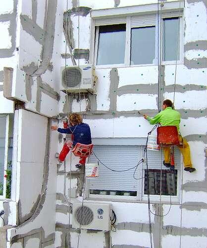 Des ouvriers du bâtiment en train de poser des panneaux d'isolation. Un programme d'amélioration thermique du bâtiment favoriserait l'emploi dans ce secteur, réduirait les dépenses énergétiques domestiques et nationales et favoriserait le développement d'une économie verte. © Hyaground CC by-nc-sa