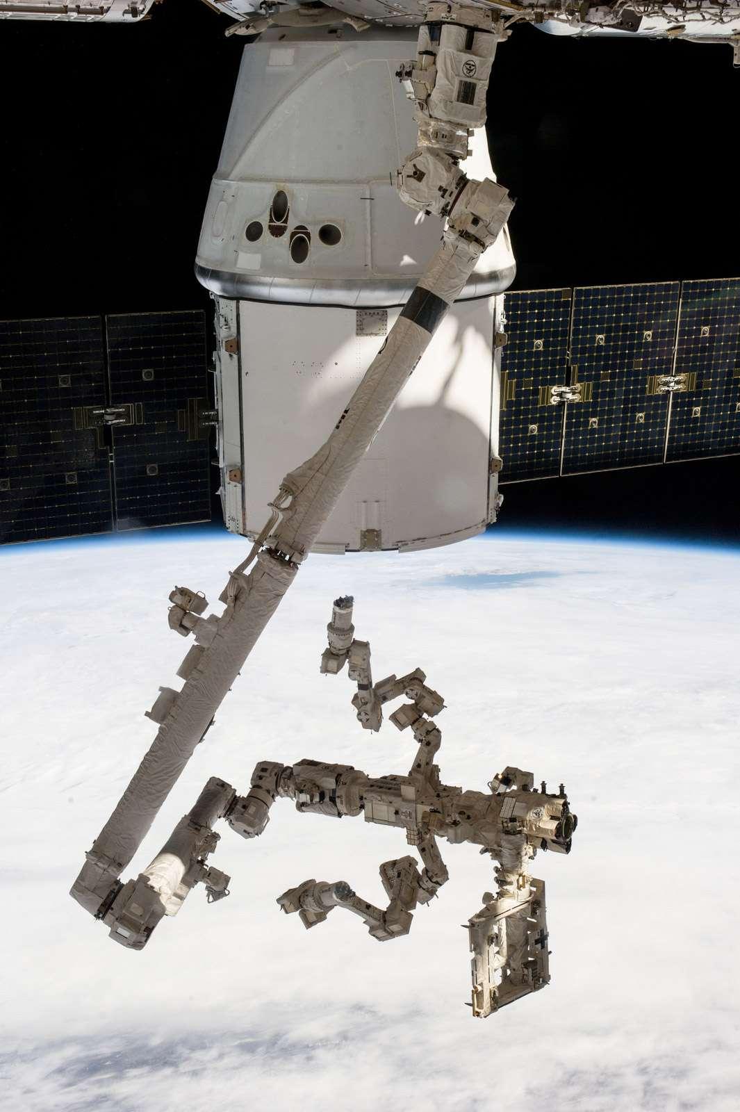 La capsule Dragon avec au premier plan le bras robotique de la Station (Canadarm 2) et, installé dessus, Dextre, s'apprêtant à extraire les deux expériences scientifiques situées à l'arrière de la capsule de SpaceX. © Nasa