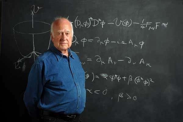 Peter Higgs posant devant les équations décrivant son boson. Crédit : resonaances.blogspot.com