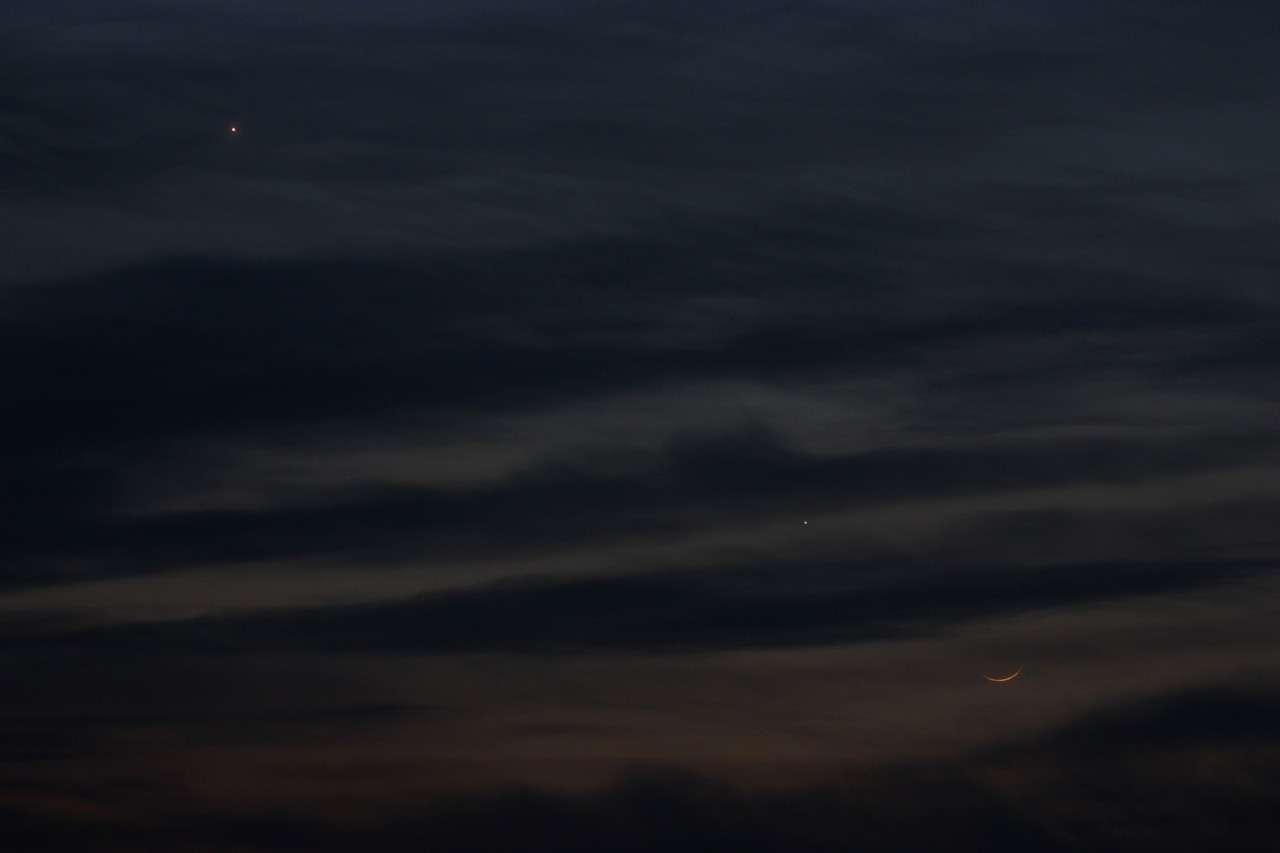 Le 15 avril 2010, quelques petites trouées entre les nuages permettent de saisir un joli rapprochement entre Vénus, Mercure et la Lune. © S. Wallart