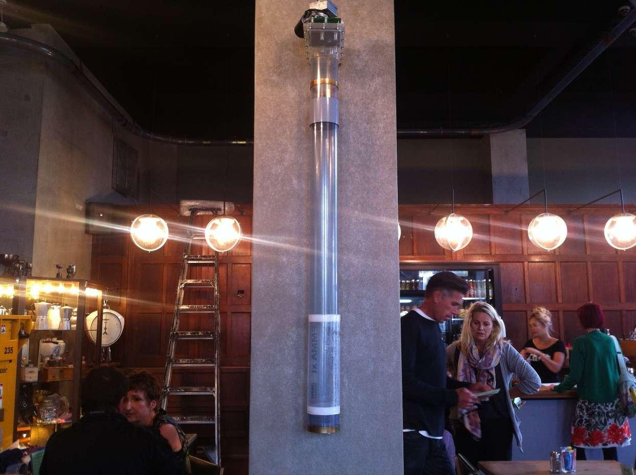 Dans ces tubes au milieu de la salle, des hamburgers dans des boîtes métalliques acheminés à 140 km/h ! © C1 Café