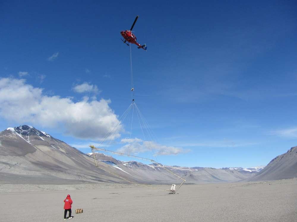 Sur le site Bull Pass, dans la vallée Wright, l'une des vallées sèches de McMurdo, en Antarctique, un hélicoptère emporte le capteur aéroporté électromagnétique (ou AEM pour airborne transient electromagnetic, en anglais). L'engin a été conçu par l'université danoise d'Aarhus avec l'entreprise SkyTem. Il permet de dresser des cartes des réseaux aquifères. Sur ce continent du pôle Sud, il a décelé un grand nombre de poches de saumure dans le sous-sol ou sous la glace. © Jill Mikucki