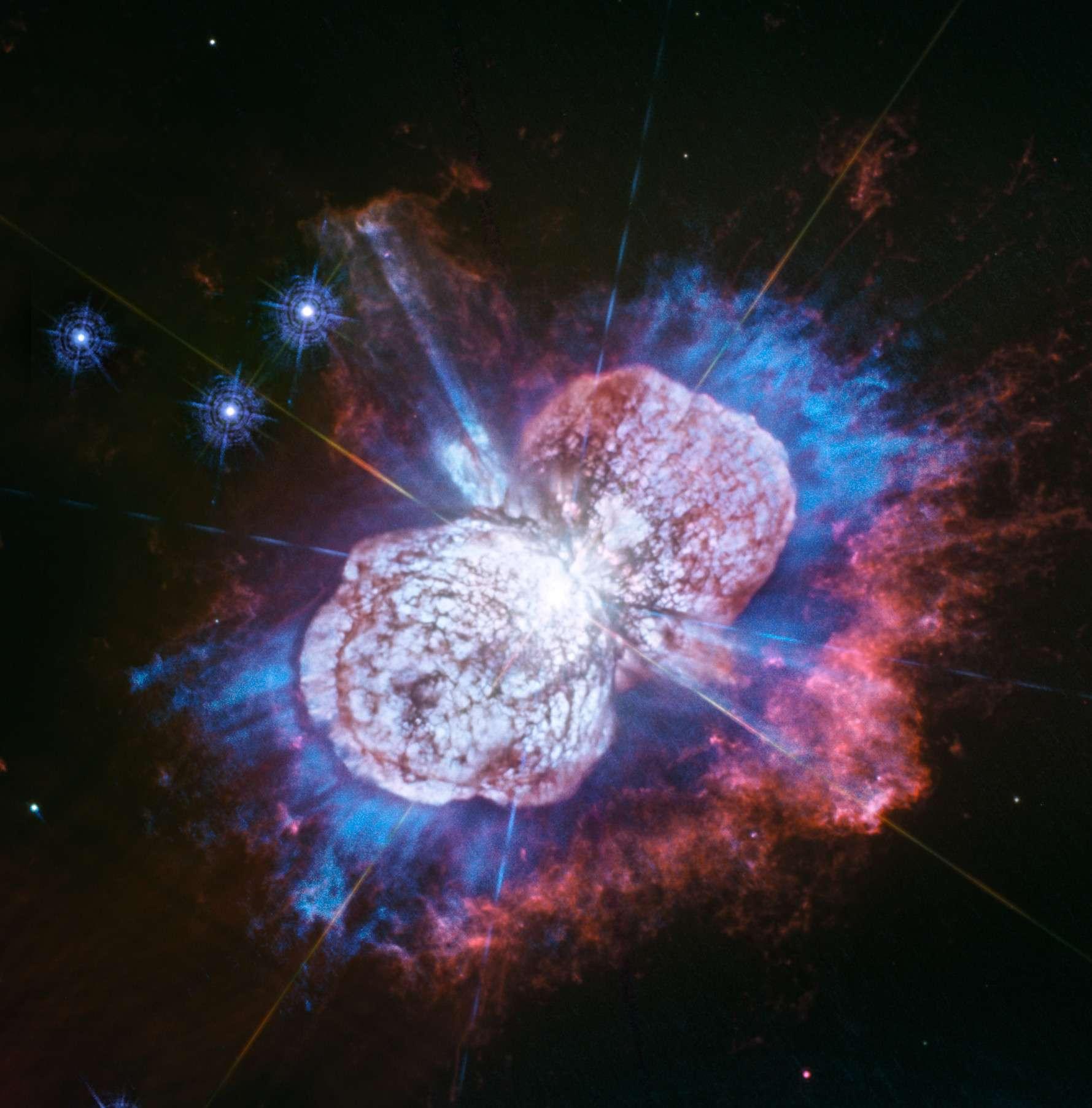 La nébuleuse de l'Homoncule créée par l'explosion de l'étoile principale du système stellaire d'Eta Carinae vue dans l'ultraviolet par Hubble contient une masse de gaz riche en magnésium (bleu) jusque-là insoupçonnée par les astronomes, située dans l'espace entre ses lobes de gaz et de poussière (blanc-rose) et les filaments d'azote (rouge). © Nasa, ESA, N. Smith (University of Arizona, Tucson), and J. Morse (BoldlyGo Institute, New York)