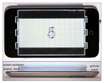 Les chercheurs de l'université de Berkeley ont positionné sur l'écran d'un iPod touch leur prototype de filtre micro-perforé. Il est placé sur un support transparent de quatre millimètres et est recouvert par un écran de protection. L'ensemble vient doubler l'épaisseur du baladeur d'Apple. © Fu-Chung Huang