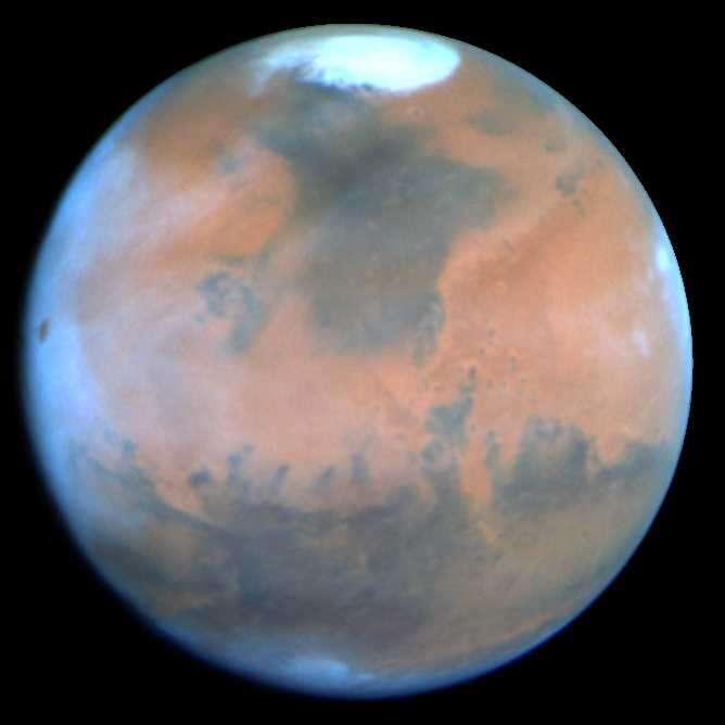 La planète Mars vue par le télescope Hubble en 1995. Cette image d'une exceptionnelle qualité ne nous montre ni visage ni canaux, mais la calotte polaire nord ainsi que de très nombreuses formations. Des nuages matinaux sont visibles sur le bord gauche. Crédit Nasa, Philip James, Université de Toledo; Steven Lee, Université du Colorado