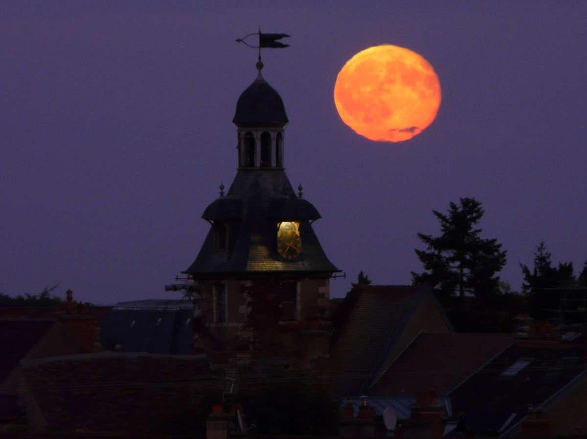 Lever de Pleine Lune photographié le 13 octobre en soirée au-dessus du beffroi de Nuits-Saint-Georges (Côte d'Or). On distingue un petit rayon vert au sommet du globe lunaire. © J.-B. Feldmann