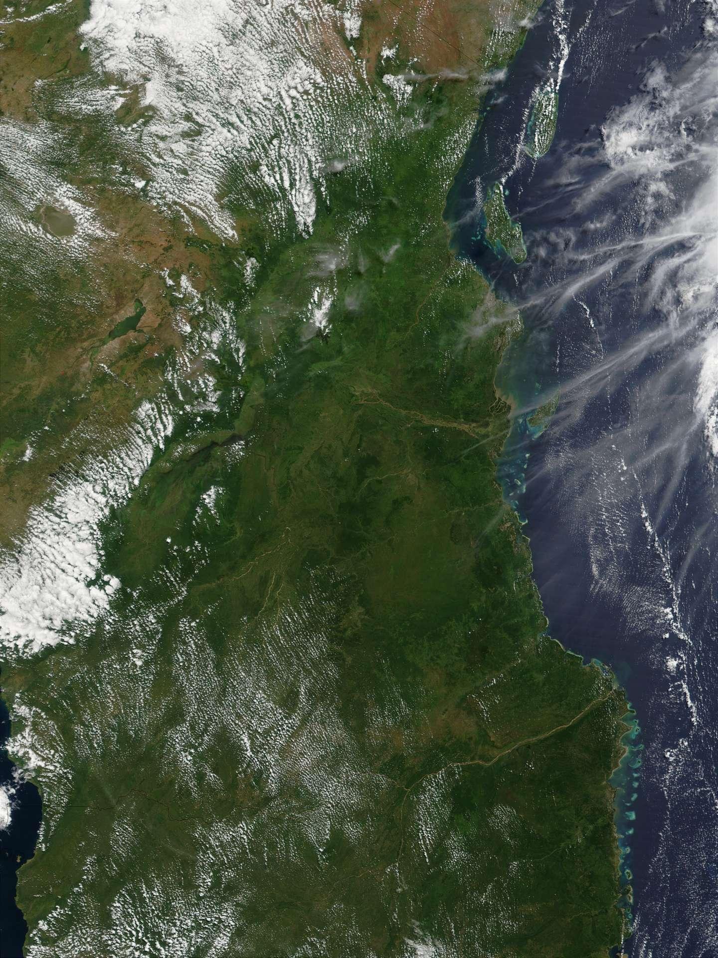 En haut à gauche de cette photo de la Tanzanie, la plaine du Serengeti se dresse derrière les nuages. En bas à gauche, le lac Malawi traverse la Tanzanie au nord jusqu'au Mozambique au sud. De nombreuses traînées d'avions dessinent des lignes blanches au dessus de l'océan Indien, à droite de l'image. © Nasa, 2002