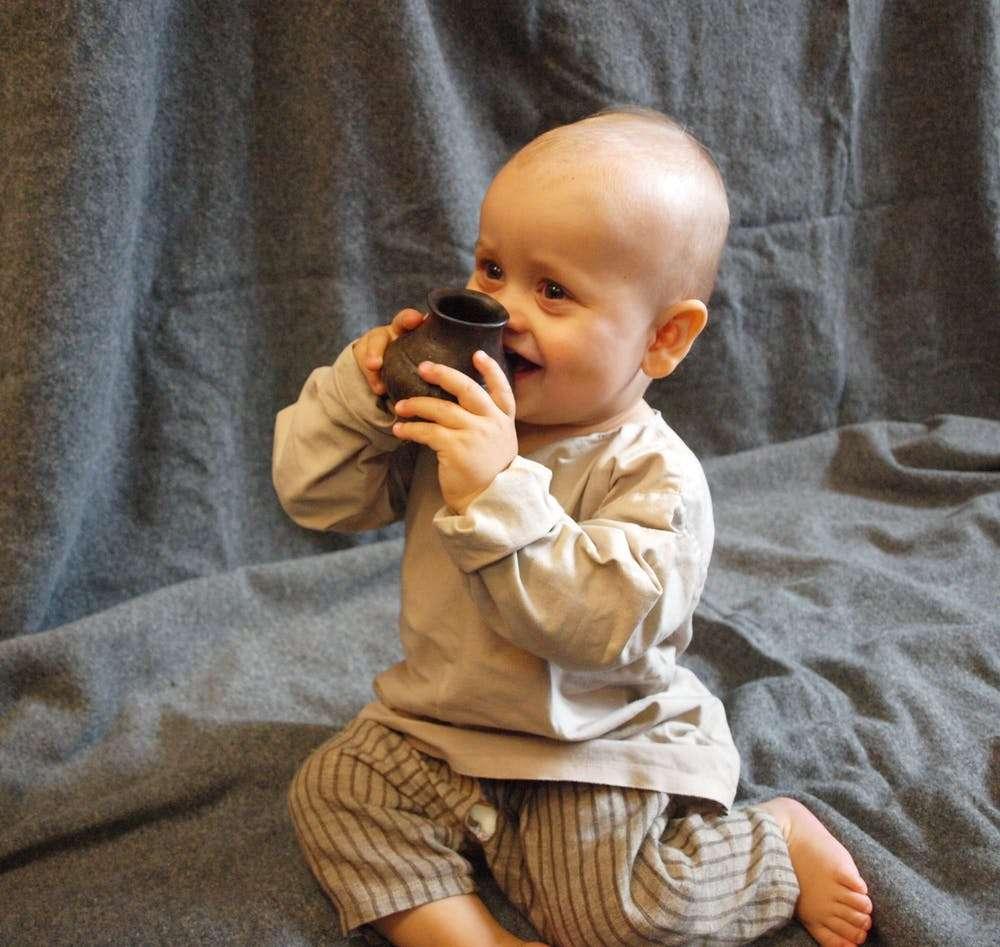 Des traces de lait de ruminants ont été retrouvées dans des biberons en céramique datés de 5.000 ans avant J.-C. Ici, un bébé avec une reconstruction d'un de ces récipients préhistoriques. © Helena Seidl da Fonseca