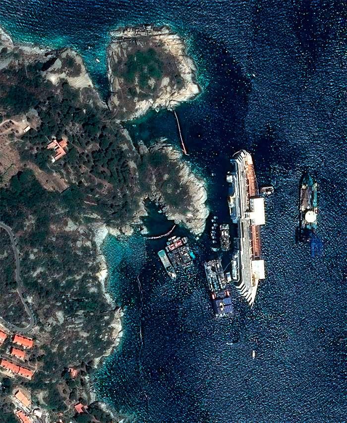 Le Costa Concordia est un paquebot de 290 m de long. L'opération pour le relever, par effet levier, est une entreprise titanesque. Ci-dessus, un montage de deux images satellite : le navire lors de l'opération de remise à flot le 17 septembre (à droite), et une vue plus large de son emplacement aux abords de la côte de l'île de Giglio en juillet 2013 (à gauche). © Astrium Geo