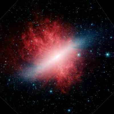 """Image infrarouge du télescope spatial Spitzer On y voit la """"galaxie du cigare"""" (en bleu), enrobée d'un gigantesque halo de particules (en rouge) (Crédits : NASA/JPL-Caltech/University of Arizona )"""