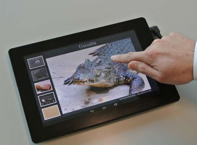 Fujitsu a profité du Mobile World Congress pour présenter son prototype de tablette dont l'écran tactile délivre un effet haptique qui reproduit certaines sensations du toucher. Quatre démonstrations permettaient de ressentir les cordes d'un instrument de musique, les boutons d'une table de mixage de disc-jockey, la serrure d'un coffre-fort ainsi que la peau d'un crocodile. © Fujitsu Laboratories
