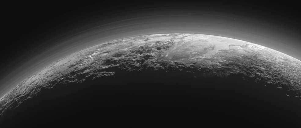 Cette image de Pluton a été prise par la sonde New Horizons le 14 juillet 2015, à quelque 18.000 km de distance, 15 mn après le survol de la région Tombaugh et de la plaine Spoutnik. On aperçoit une partie de cette dernière, sur le limbe, à droite. Les montagnes qui la bordent, en bas et à sa gauche (est) sont Norgay Montes. Plus haut, sur l'horizon, on distingue Hillary Montes. Par-dessus, on compte, dans son atmosphère riche en azote, plus d'une douzaine de couches de brume jusqu'à 100 km d'altitude. L'image couvre une portion de 1.250 km. Téléchargez l'image en haute résolution ici (3,7 Mo). © Nasa, JHUAPL, SwRI
