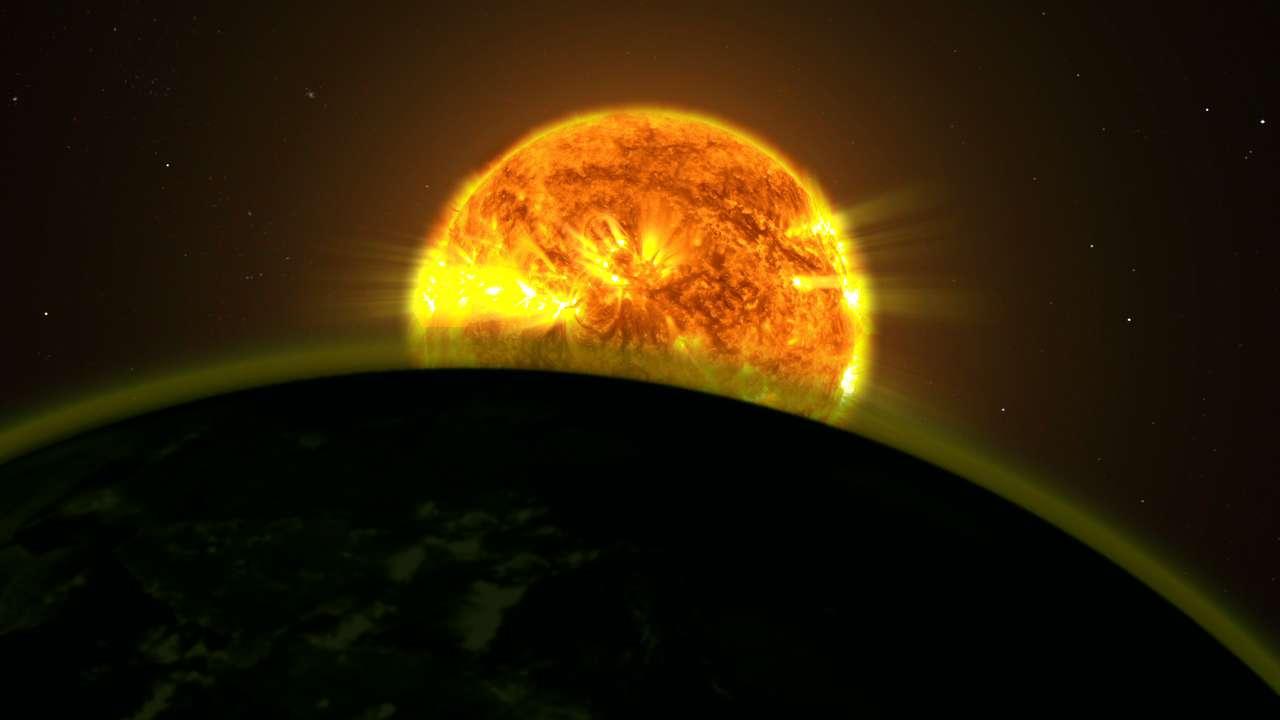 Une vue d'artiste du transit d'une exoplanète devant son étoile hôte. La lumière qui passe à travers son atmosphère est partiellement absorbée par les molécules qui y sont présentes. En utilisant des méthodes spectroscopiques, on peut détecter les raies d'absorption de ces molécules et en déduire la composition chimique de l'atmosphère. Hubble a ainsi démontré la présence de molécules d'eau dans cinq exoplanètes. © Nasa