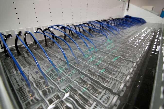 Des serveurs en racks alignés dans le bac à bain d'huile mis au point Green Revolution Cooling. À l'extérieur, un échangeur thermique assure la circulation et le maintien de la température à 40 °C. © Green Revolution Cooling