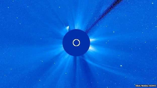 Dans la nuit du 28 au 29 novembre, l'observatoire solaire Soho repérait un éclat, que l'on voit ici en haut à gauche du disque masquant le Soleil. La trajectoire de la comète Ison vient d'en bas à droite sur cette image. Débris de queue voué à disparaître, ou fragment survivant du noyau ? On l'ignore encore, mais il est certain que la comète s'est en partie disloquée. © Nasa
