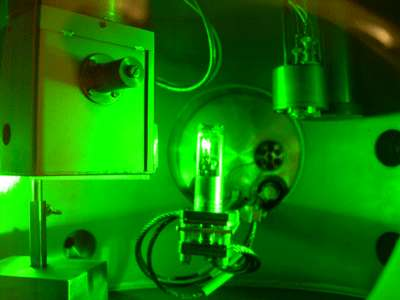 Du deutérium dense est irradié par un laser. L'éclat blanc dans le récipient au centre de la photo provient du deutérium. Crédit : Leif Holmlid-Atmospheric Science, Department of Chemistry, the University of Gothenburg