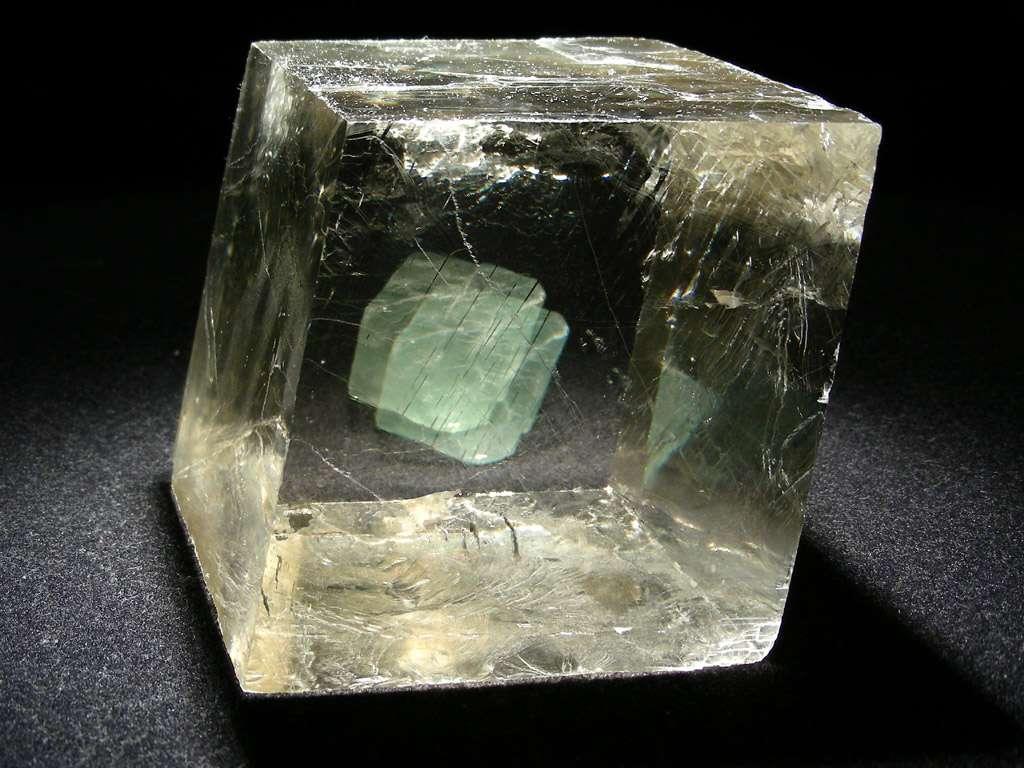 Le buzz de l'année 2011 : la pierre de Soleil des navigateurs vikings ne serait pas un mythe. Avec l'octaèdre de fluorine verte placé derrière, on voit bien la biréfringence de la calcite optique ou spath d'Islande. © www.carionmineraux.com