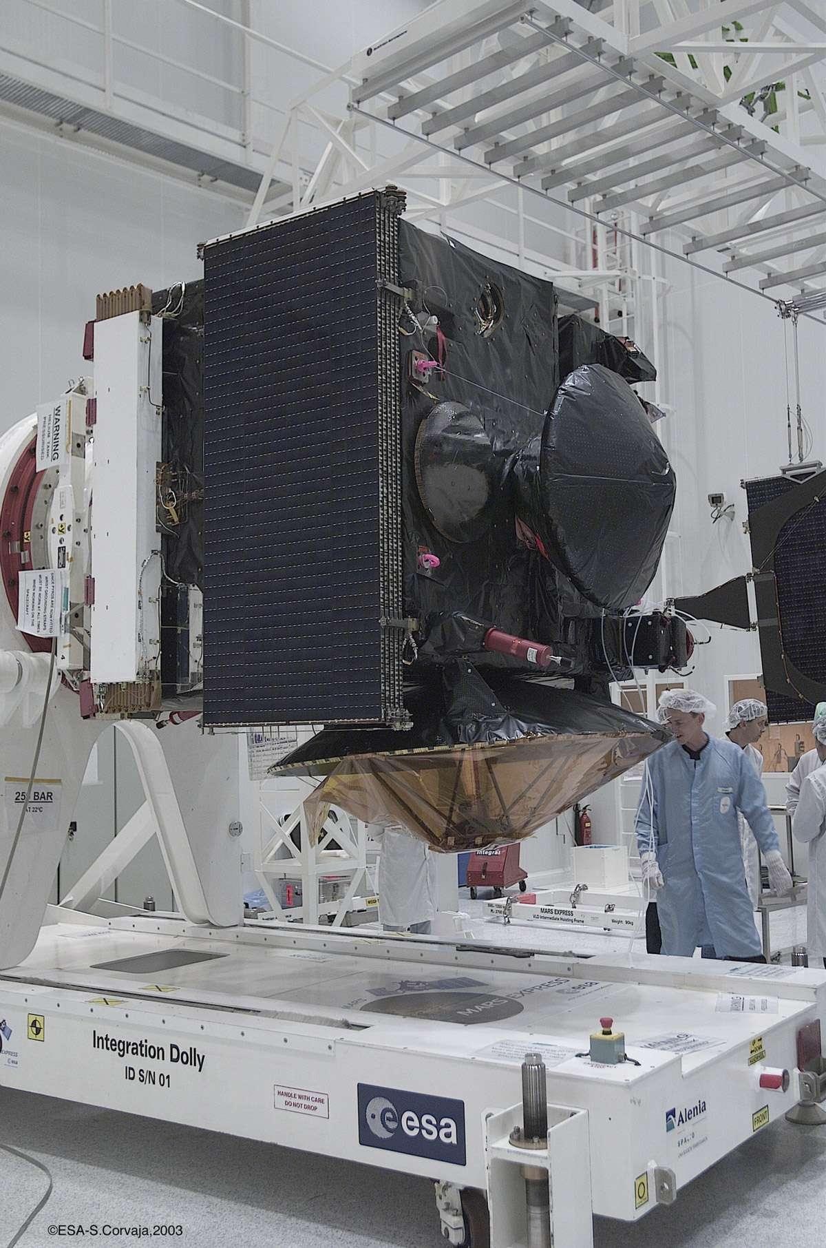 De forme parallélépipédique, de 1,5 x 1,8, x 1,4 m de côté, la sonde Mars Express est équipée de deux panneaux solaires déployables. Son radar Marsis est muni de deux antennes d'environ 20 m. On la voit ici dans les locaux de Starsem, à Baïkonour, quelques semaines avant son lancement. Beagle-2 est installé sur la face de la sonde, entouré d'un plastique noir (à ne pas confondre avec l'antenne grand gain qui fait face au sol). © S. Corvaja, Esa