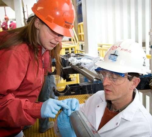 La microbiologiste Maria-Cristina Ciobanu et le géochimiste Simon George examinent une carotte. Crédit Consortium for Ocean Leadership